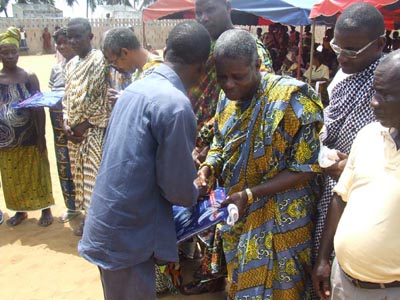Dr Tia of the CEMV putting back(handing) a mosquito net to a notable of Azu