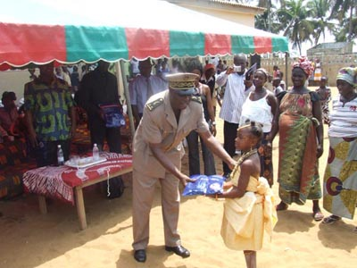 Administration official symbolically presenting a mosquito net to a young girl.